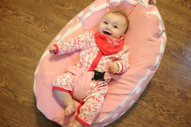 smiling baby girl lying on bean bag wearing white footless sleepsuit with red doodle pattern and a red bib with a white butterfly
