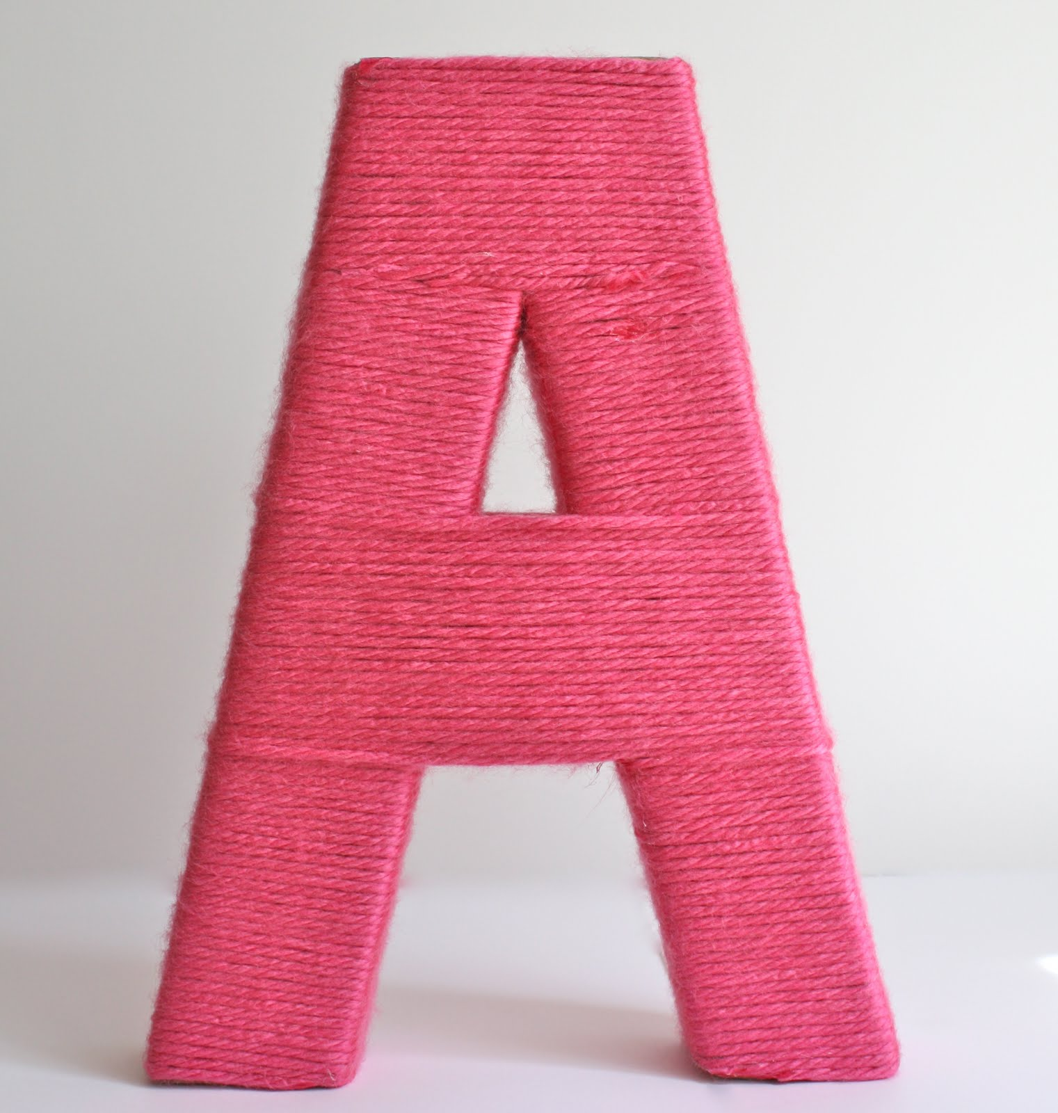 letters covered in yarn Thank goodness i was allowed to take up the entire kitchen table at amy and brian's once we landed and was able to enlist another adorable neice, miss abigail milkes as my craft assistant she made sure every inch of the letters were covered and helped me match the yarn and the fabric flowers together.