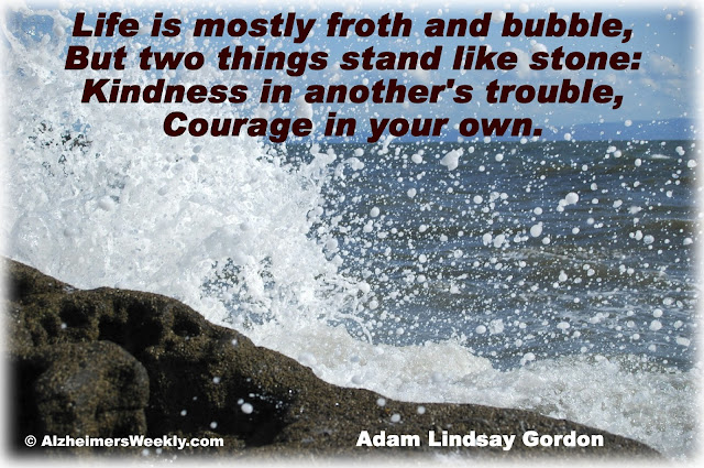 Ocean spraying on boulders with saying about kindness and courage