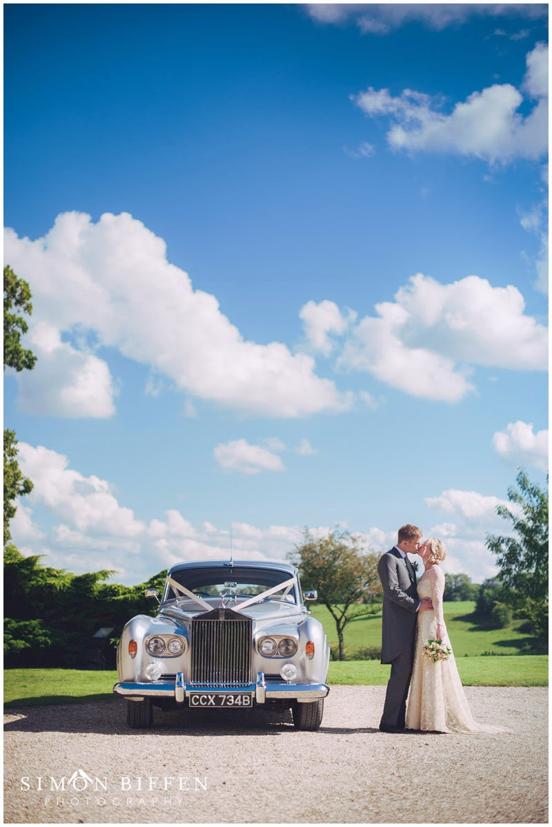 Bride and Groom kiss with Rolls Royce at Ston Easton Park