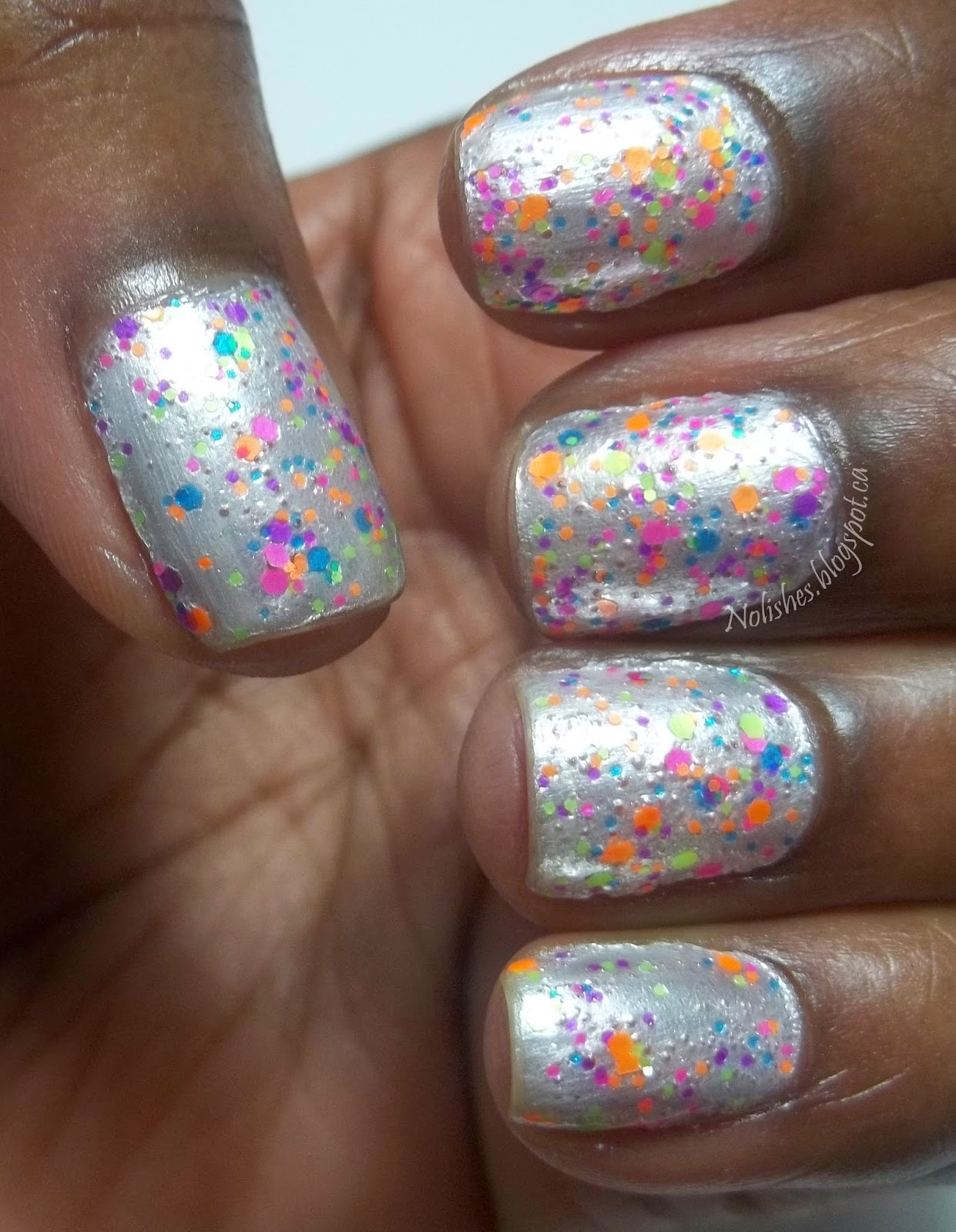 White frost base polish topped with silver micro glitter, and then a neon rainbow glitter
