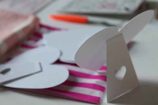 white heart shaped place cards with cut out heart detail on stand