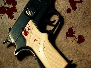 A gun on the murder scene with blood stains.