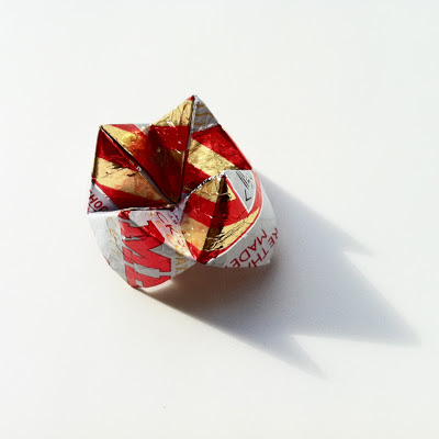A stripy red and gold wafer wrapper that has been folded in an origami style, partially showing the writing on the wrapper.