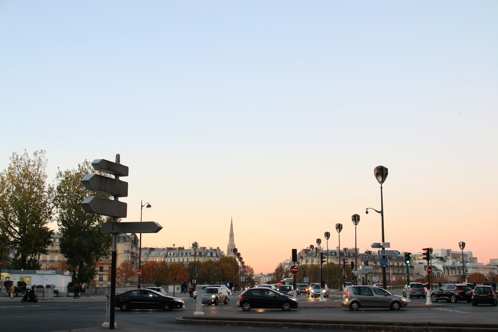 cars driving through a main road in paris during sunset