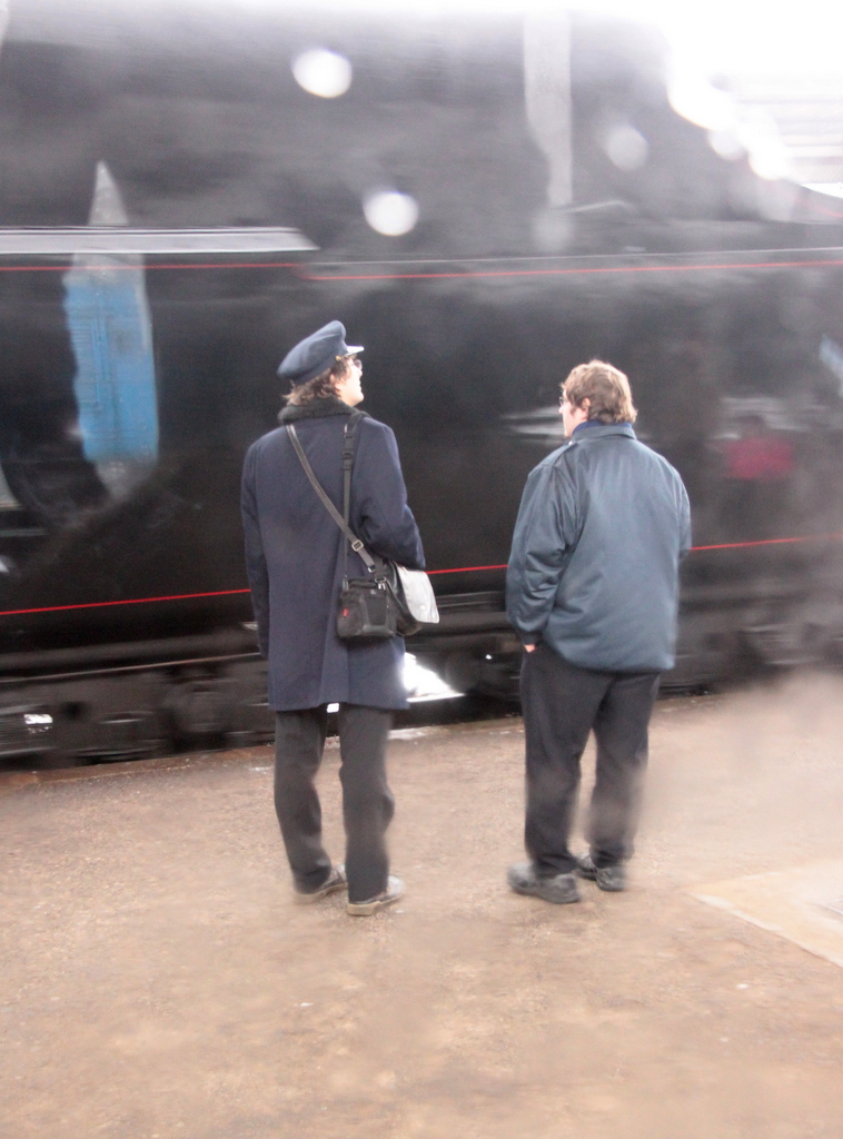 conductors watch a steam train in Beroun Czech Republic