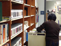 woman shelving library materials from a cart
