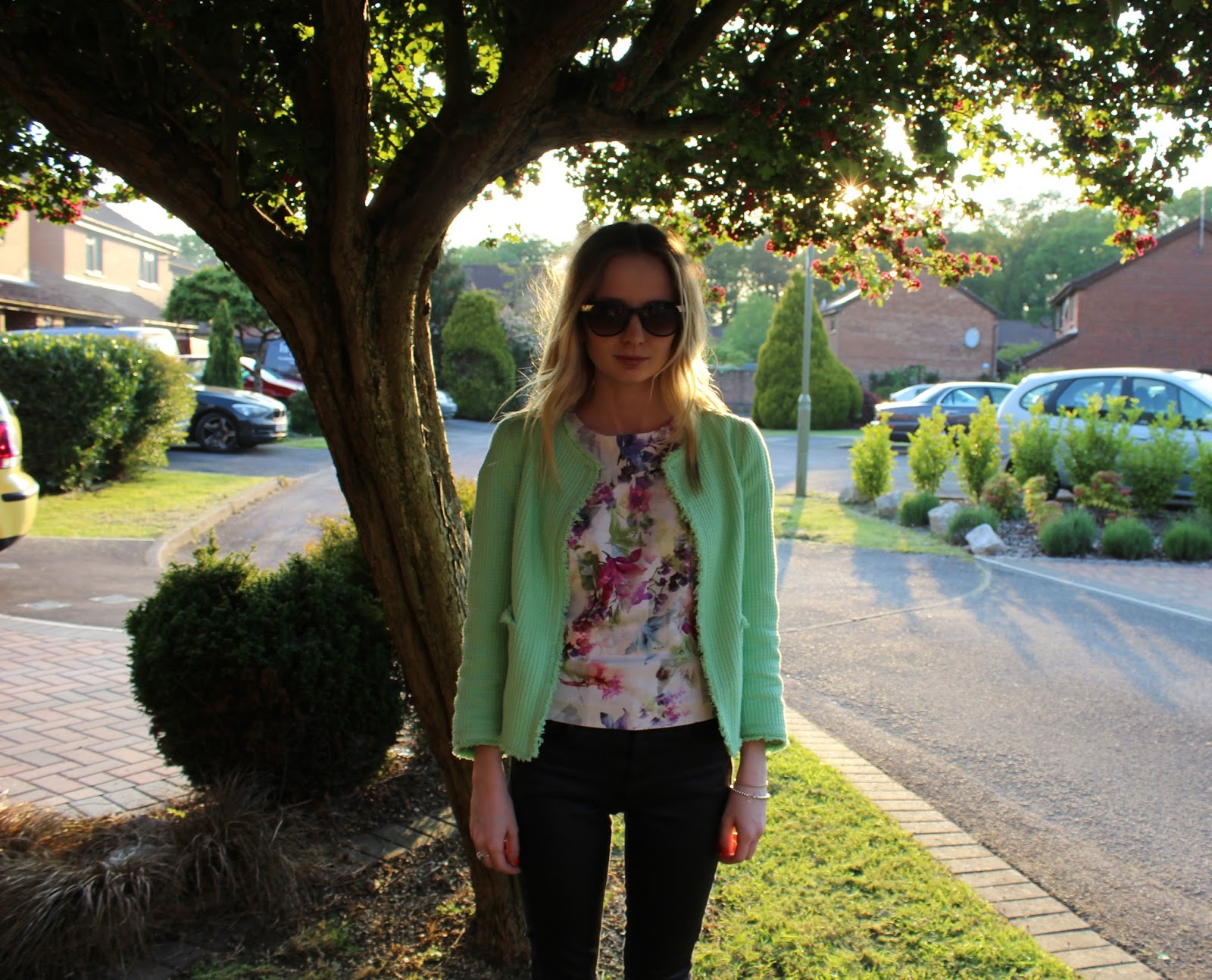 Close up of girl wearing zara green jacket and warehouse floral shell top