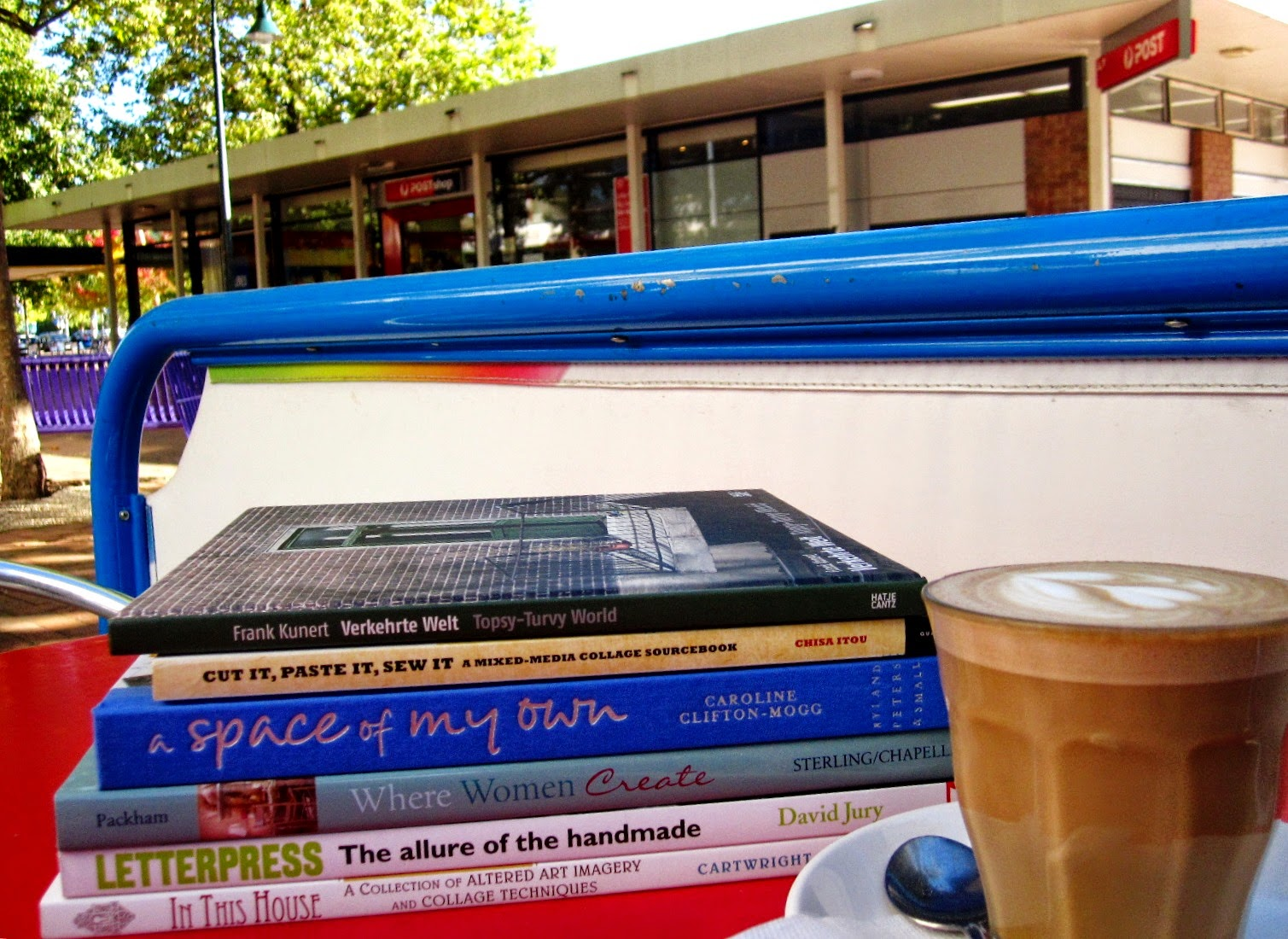 Outside cafe table containing a pile of six new books and a cup of coffee, overlooking Dickson Post Office.