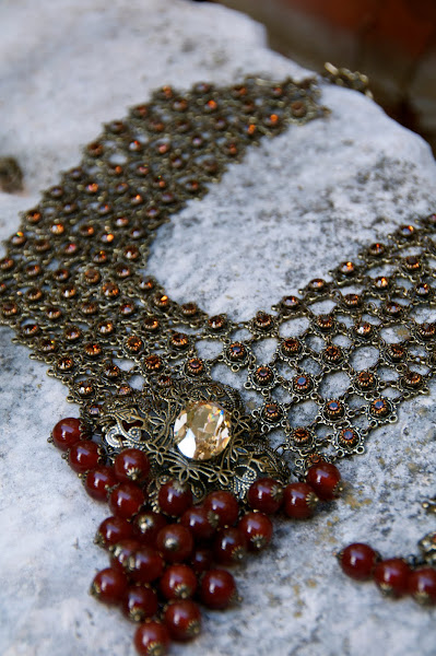 Links of flowers connect amber crystals and carnelian beads.