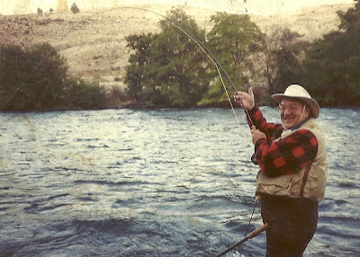 A picture of Don Wilson standing in the Deschutes River landing a steelhead with his fly rod.