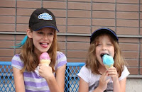 Image -Kawartha Dairy Icecream cones being enjoyed by two young girls on a bench, one wearing a Kawartha Dairy baseball capj.