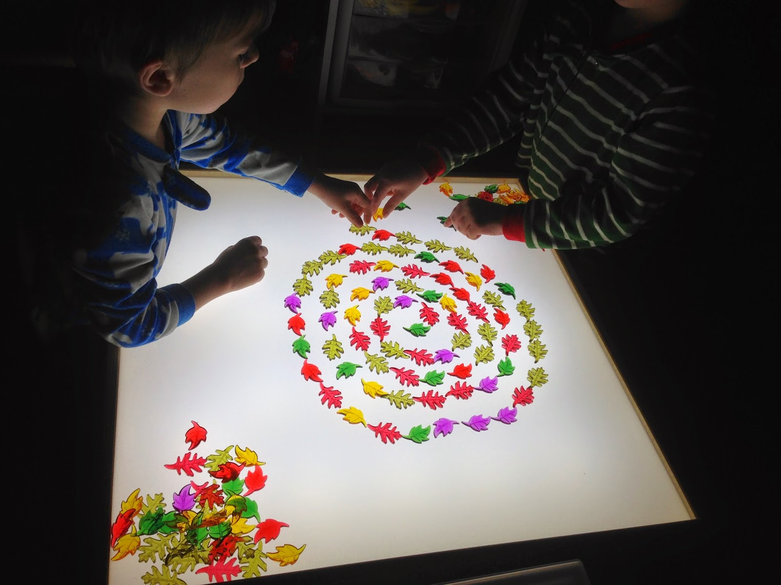 twins playing on the light table