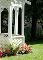 The manicured lawns of the sideyard at Marigold Springs boast a white latice-work gazebo, perfect for brial photos