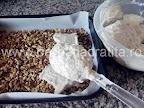 Prajitura Deliciu cu crema si biscuiti Preparare blat din nuca - turnam in tava compozitia