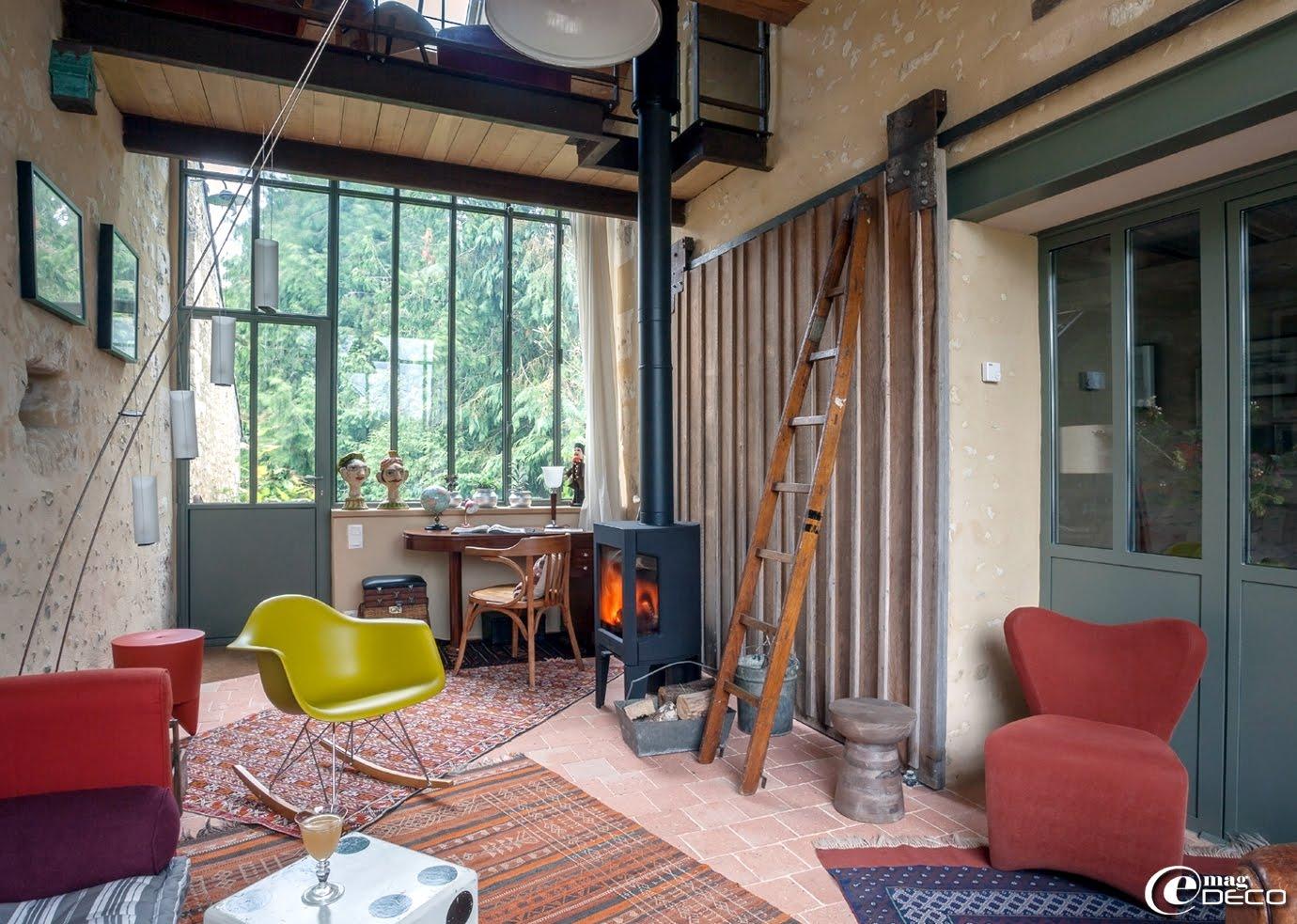 Dans un des salons lumineux de 'La Maison d'Hector' une chaise à bascule RAR 1950 design Charles et Ray Eames rééditée par Vitra et une verrière métallique conçue par la 'Métallerie Fertoise'