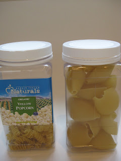2 clear jars with white lids filled with pasta