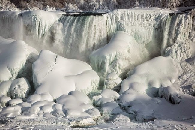 The falling water collected and froze under the falls, creating these huge ice formations. - Bizarrely Low Temperatures Transformed Niagara Falls Into A Frozen Wonderland