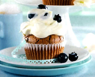 Chocolate cupcakes with a yoghurt frosting topped with blueberries.