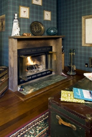 romantic wood fireplace with burning log, plaid blue wallpaper,