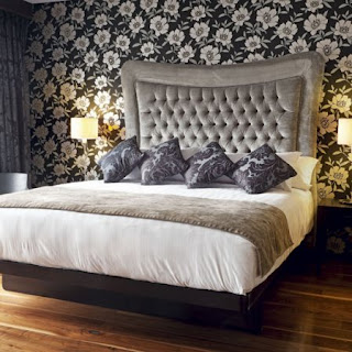 The elegant bedhead is softened with the floral matching silver and black wallpaper. The deep diamond buttoning detail and large upholstered bedhead is softened with the wallpaper.