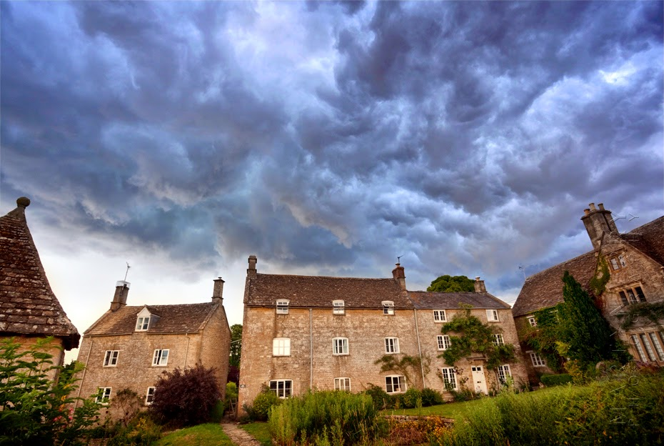 Wide angle shot of Cotswold houses and storm clouds