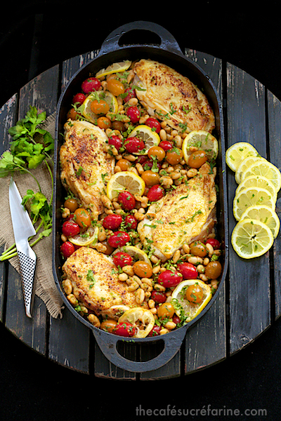 Overhead photo of a black cast iron pan filled with Mediterranean Roasted Chicken Breasts on a round wooden table with cilantro and lemon slices next to the pan.