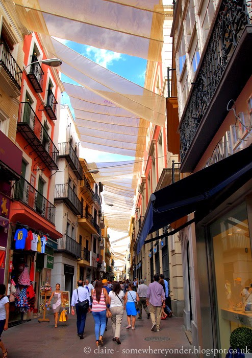 Walking through the central city, fabric floating overhead to keep off the heat of the day - Seville