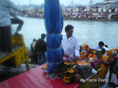 Priests sitting on raised wooden planks at the Har Ki Pauri Ghat in Haridwar