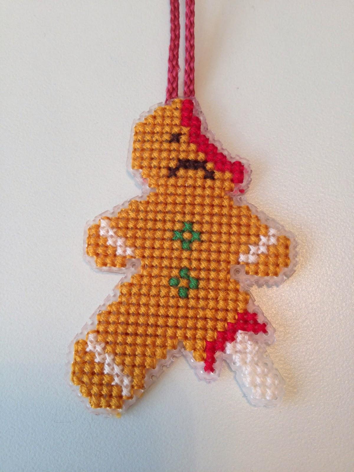 Julepynt med humor. Halvspist maltrakteret kagemand i korssting broderi. På plastik kanvas.