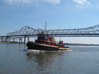 The busy Mississippi River with tugs, barges and oil tankers.