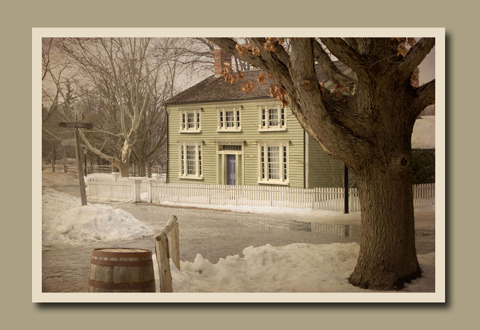 A view of Burwick House in the snow from under a large old oak tree at Black Creek Pioneer Village.  Holly Cawfield Photography