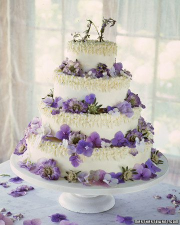 colored round four tier wedding cake with and array of pretty purple