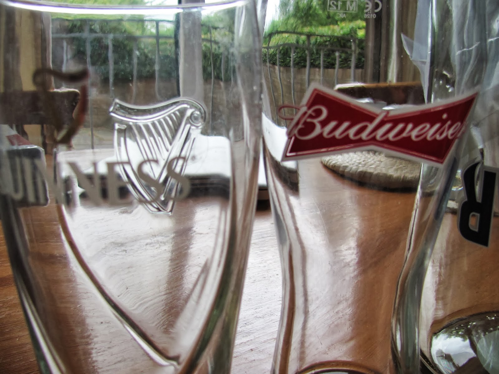 An empty Guinness glass and an empty Budweiser Glass on our kitchen table in Dublin, Ireland