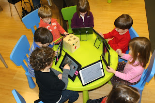 Kids around a table using Ipads