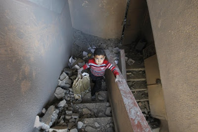 Palestinian boy surrounded by rubble