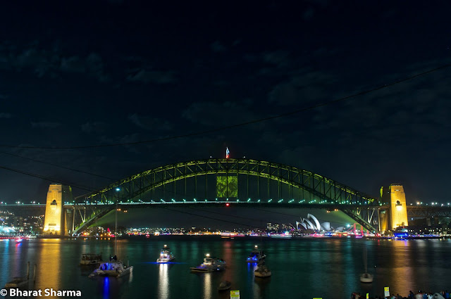 It was New Year, when Bharat and Ishita flew to Australia from New Zealand for celebrations. This Photo Journey shares some of the moments from Sydney Harbour, where some amazing fireworks were captured on New Year Evening. Let's check out more from Sydney Harbour.Above photograph shows Sydney Harbour Bridge which is basically a steel bridge through arch bridge across Sydney Harbour that carries rail, vehicular, bicycle and pedestrian traffic between the Sydney central business district (CBD) and the North Shore. The dramatic view of the bridge, the harbour, and the nearby Sydney Opera House is an iconic image of Sydney, New South Wales, and Australia. The bridge is nicknamed 'The Coathanger' because of its arch-based design.In midnight, Australia celebrates the start of a New Year! Sydney does this in style by lighting up the night sky with a spectacular fireworks display launched from seven barges on the Harbour, the rooftops of seven city skyscrapers and, unforgettably, from Sydney Harbour Bridge. It becomes a  reason why Sydney is the New Year's Eve Capital of the World.Many of the folks come to Australia for New Year Celebrations. Many folks don't get right place at Sydney Harbour foreshore to watch what is clearly the best New Year's Eve fireworks display on Earth. This firework shows is quite popular and there are some online services providers who stream live view from a great place and these models work very well.Dawes Point, Garden Island, Sydney Cove and Vaucluse are some of the main places at Sydney Harbour. Few helicopter cameras keep capturing the great moments for online folks. The bridge's design was influenced by the Hell Gate Bridge in New York. It was the world's widest long-span bridge, at 48.8 meters wide, until construction of the new Port Mann Bridge in Vancouver. It is also the fifth longest spanning-arch bridge in the world, and it is the tallest steel arch bridge, measuring 134 metres from top to water level. Until 1967 the Harbour Bridge w