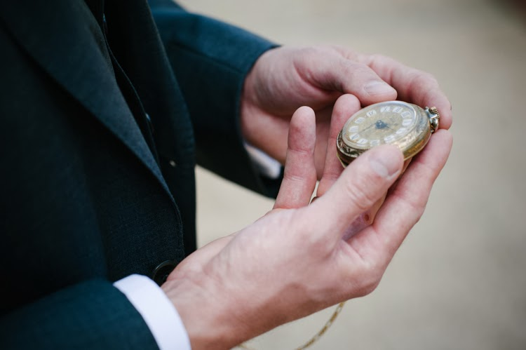 groom holding his great grandfather's antique gold watch