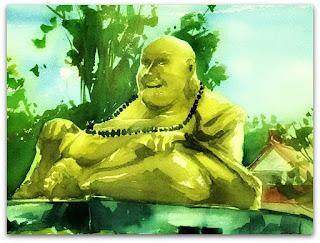 Estátua dourada de monge sentado com as pernas cruzadas, em posição de meditação.