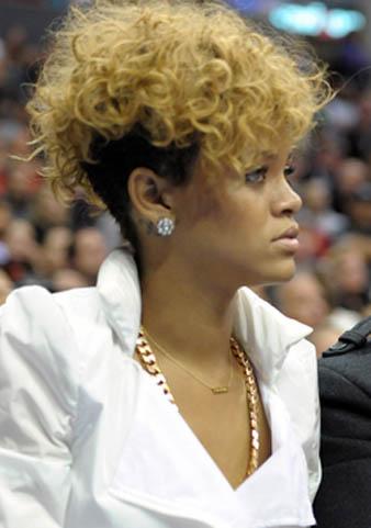 Rihanna mohawk tarzı saç kesimin öncüsüdür diyebiliriim ve yine mohawk tarzı kazıtılmış saçları ile karşımıza çıkan Rihanna bu defa saçlarının üst kısmını daha uzun tutmuş ve sarıya boyatmıştır. İşte bu sarı saçlara kıvırcık model verdiren Rihanna her zaman olduğu gibi yine çılgın tarzı ile hayranlarını şaşırtmıştır.