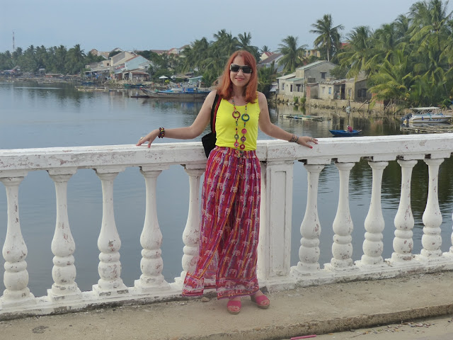 Colourful print gypsy palazzo pants worn with yellow top and bright necklace
