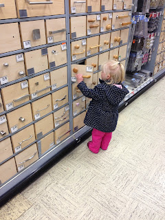 Small child looking at handles in Homebase