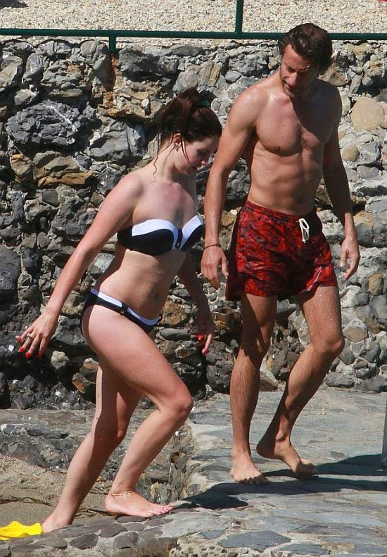 The 28-year-old showcased her impressive body in a white bikini and black line as she soaked up the sun with boyfriend, Francesco Carrozzini in Italy on Thursday, July 3, 2014.