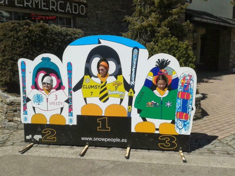 la imagen muestra a tres niños posando en un fotomontaje que simula un podio de esquí