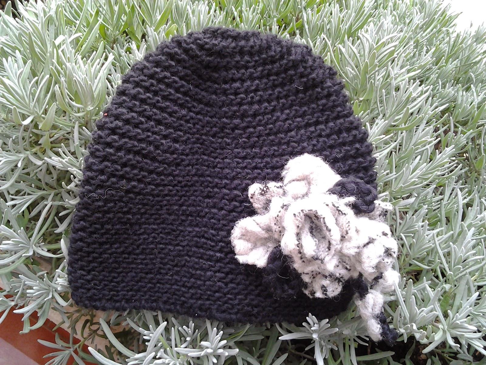 Cappello a maglia legaccio in morbida lana nera con applicazione di fiore  in lana cotta. 2a619b9c1ded