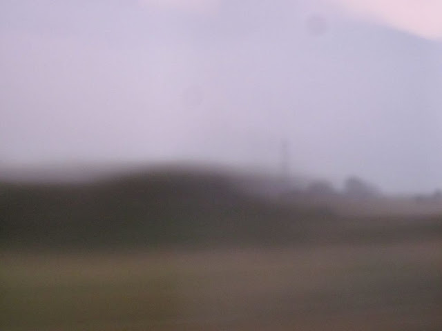 Blurry view from a coach window. Brown, green and grey.