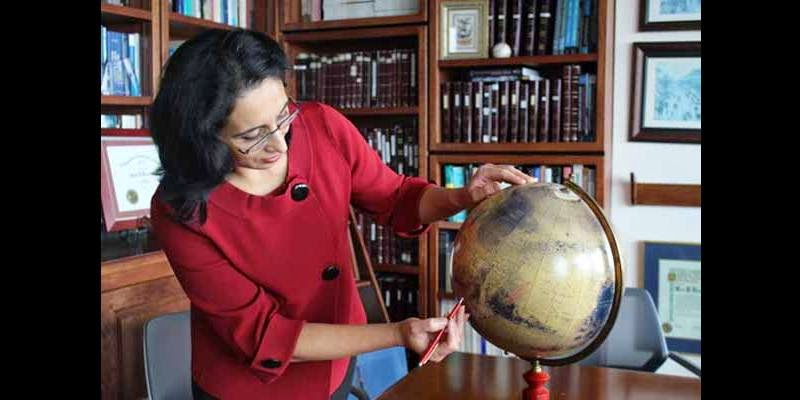 Robina Shaheen searches a globe of Mars for the likely origin of the Mars rock she and colleagues analyzed for traces left by the planet's early climate. Credit: Susan Brown, UC San Diego.