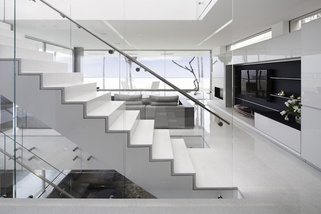 Modern staircase in the Flip Flop House with glass rail and Terrazzo covered floor