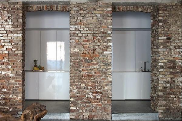 Ściana z  surowej cegły oddziela białą kuchnię od reszty loftu