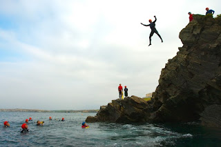 Man Jumping Off A Cliff Into the Sea - Coasteering